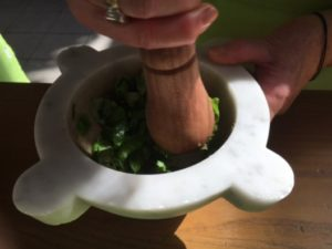 Making Pesto with a mortar and pestle, photo courtesy of Victoria DeMaio