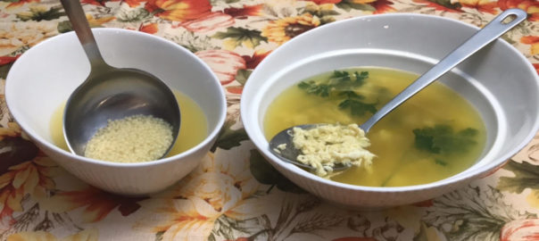 Two oval, white bowls of Chicken Soup, one with Chicken Egg Drop Soup and the other with Pastina Soup on a colorful tablecloth with fall pumpkin theeme