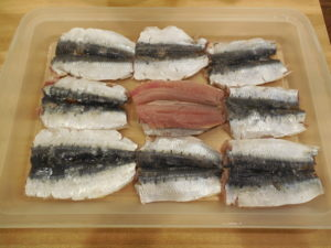Fresh Sardines are slit open, cleaned and shown lying flat before stuffing