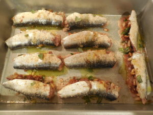 Sardines are stuffed, folded over and have been placed into a pan, ready to cook