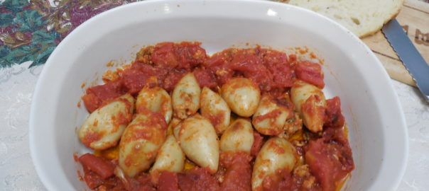 Stuffed calamari in tomato sauce in a bowl with crusty Italian bread next to it ready to sop up the sauce.