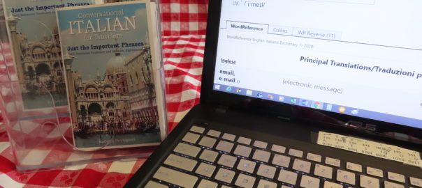 "Conversational Italian for Travelers book ""Just the Important Phrases"" standing on an open laptop computer open to an English to Italian dictionary with the definition of the word email on the screen."