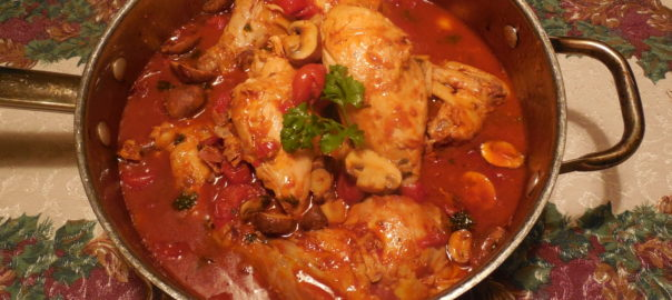 Chicken with tomato sauce that contains Marsala wine and mushrooms is shown in the pan used to cook it on a table with a flower pattern