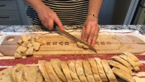 Breadboard with French bread being cut into cubes