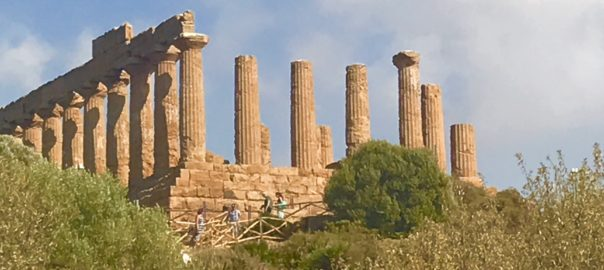 Photo of the Greek ruins at Agrigento Sicily, with tall columns reaching to a bright blue sky with puffy clouds.