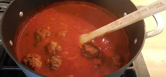 "A pot of meatballs cooking in tomato sauce on the stove. The NIAF wooden spoon with the slogan ""Make Sunday Italian Again"" is in the pot"