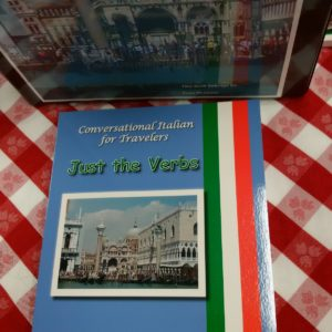 Cover of Conversational Italian for Travelers Just the Important Verbs book resting on an Italian red-checkered tablecloth