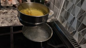 Double boiler assembly with egg and Marsala wine being whisked above the water pot
