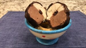 bowl with a tartufo ball cut in half so the vanilla/chocolate ice cream sides are showing with a cherry in the center.