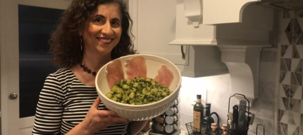 Author Kathryn Occhipinti holding a bowl of Gnocchi with Pesto alla Genovese