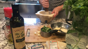 Ingredients and tools needed for making Pesto alla Genovese: Mortar and pestle as it is being used, olive oil, cheese, basil leaves